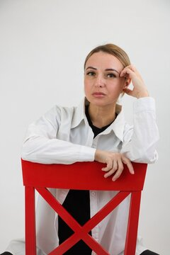 Blonde woman in light clothes sitting posing on a red chair.