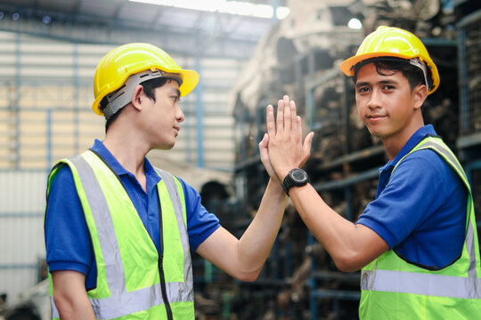 Portrait of two industrial engineer workers man wearing helmet doing high-five hand touch, standing at manufacturing plant factory with many engine parts as blurred background