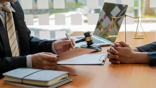 Good service, consultation of business women and male lawyers or judge advisors, having a team meeting with clients, legal concepts and a hammer with scales on the table.