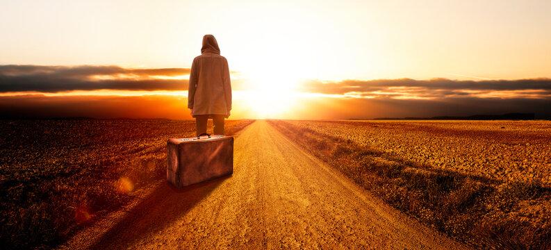 Junge Frau mit einem Koffer bei Sonnenuntergang