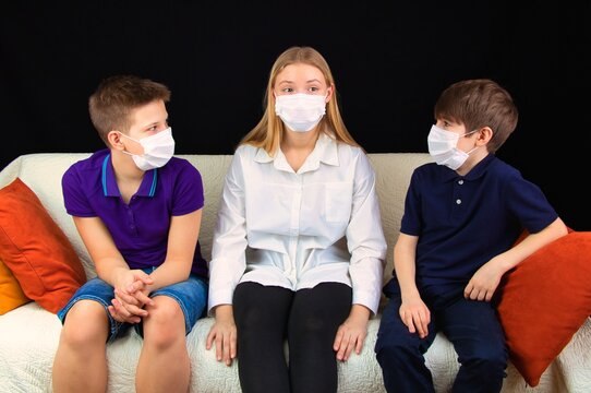 Children in medical masks sitting on the couch discussing a school assignment, close-up,