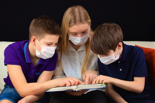 Children in medical masks sitting on the couch watching a book and discussing a school assignment.