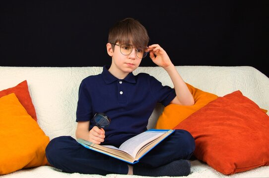 Boy in glasses and with a magnifying glass in his hand, sitting on the couch with a book.