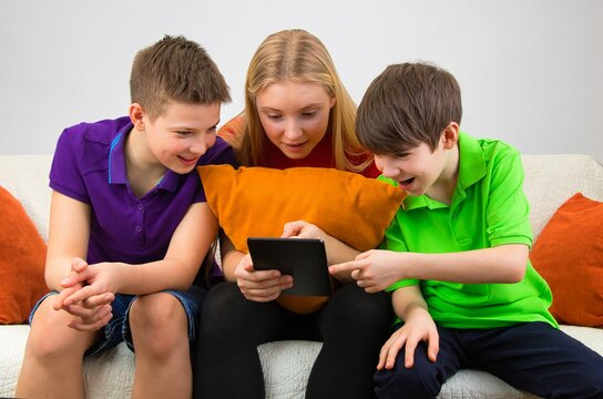 Children are sitting on the couch, looking at a tablet and discussing a school assignment.