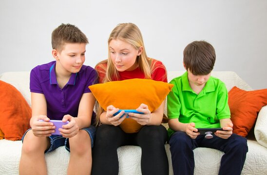 Children are sitting on the couch, looking at the phone and discussing a school assignment.