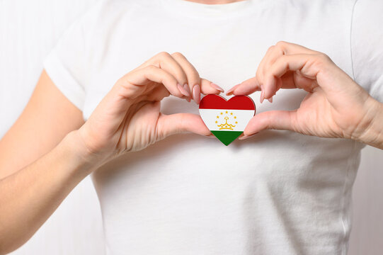 Flag of Tajikistan in the shape of a heart in the hands of a girl. Love Tajikistan. The concept of patriotism