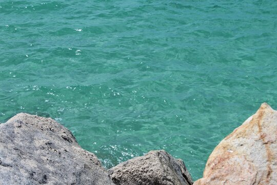 Selective focus. Beautiful crystal clear ocean water hitting the rocks on south pointe pier park in Miami Beach, Florida, copyspace