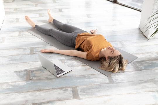 Yoga nidra practice online at home. Caucasian adult woman lying on the floor in shavasana indoor, next to her laptop, selective focus.