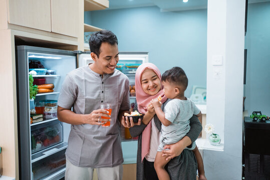 happy young muslim family having iftar breaking the fast while standing in the kitchen eating dates fruit