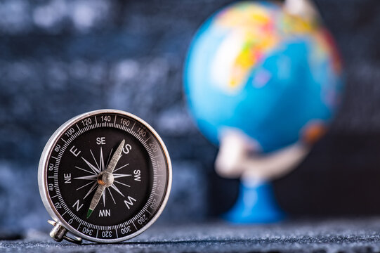 Travel planning navigation concept. Classic magnetic detail of compass on light blue with earth globe in the backround.