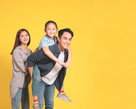 Happy Asian young family with one child standing embracing and smiling
