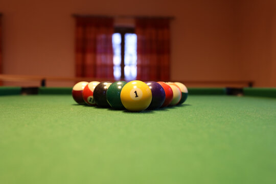Colored pool balls on a green pool table. Billiard ball with number one