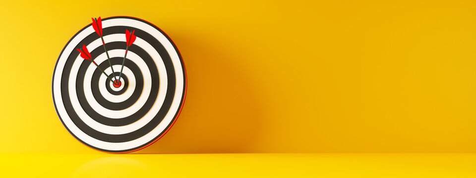 Zielscheibe mit 3 Pfeilen vor gelber Wand
