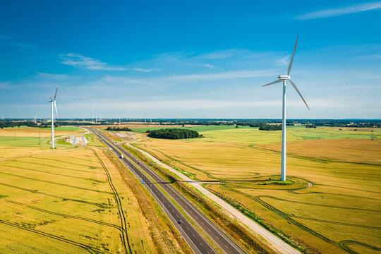 Wind turbines near highway. Renewable energy in Poland.