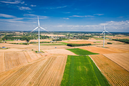 Wind turbine on field during harvest. Agriculture in Poland.