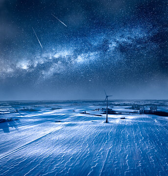 Milky way over wind turbine in winter. Alternative energy, Poland.