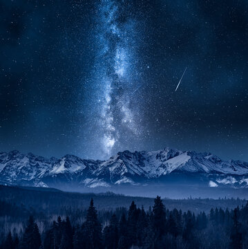Milky way over Tatras in winter. Night hiking in mountains.