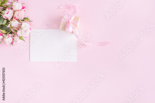 Gift box, flowers and greeting card on pink background. Flat lay. Birthday, wedding, anniversary or mother's day concept.