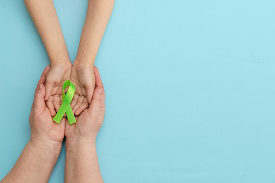 World Mental health awareness day.Adult and child hands holding Green Ribbon on blue panoramic background.Organ donation.World kidney day. Banner. Copy space. Layout. Mock up