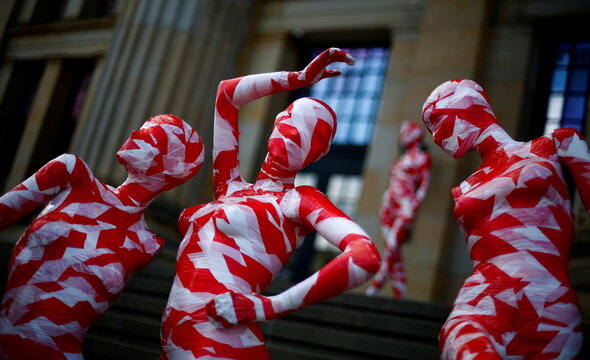 Mannequins wrapped in red and white barricade tape to symbolize the coronavirus disease crisis are placed at the Gendarmenmarkt in Berlin