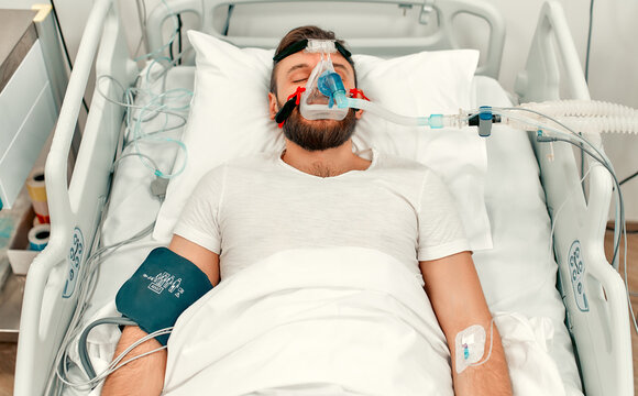 A sick man for coronavirus disease covid-19, who lies in the intensive care unit in a modern hospital with a ventilation mask.