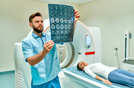 A patient lying on a CT or MRI scan and a doctor who looks at brain scans. In a medical laboratory with high-tech equipment.