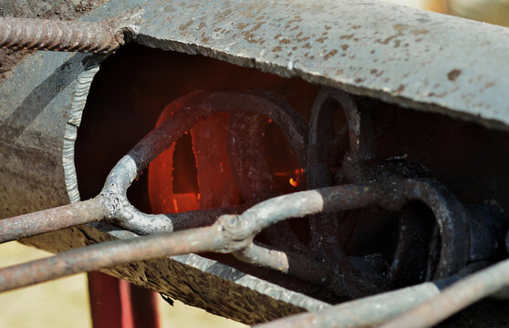 Irons glowing hot in a forge at a cattle branding event