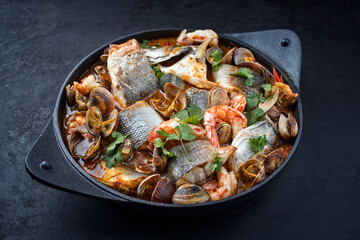Modern style traditional Spanish seafood zarzuela de pescado with fish, king prawns and venus clams served in clear sauce as close-up in design pot