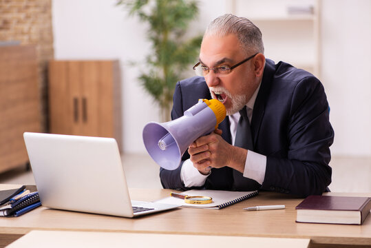 Old male employer holding megaphone