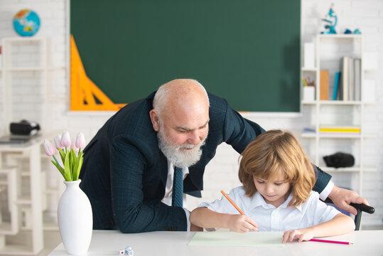 Help to learn. Schoolboy learning in classroom. School teacher, education, teachering. Pupil kid lesson.
