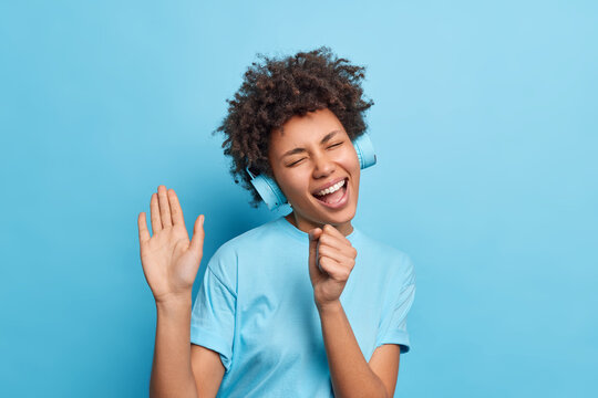 Indoor shot of carefree joyful African American woman keeps hand near mouth as if microphone sings song along closes eyes from pleasure listens music via wireless headphones isolated over blue wall