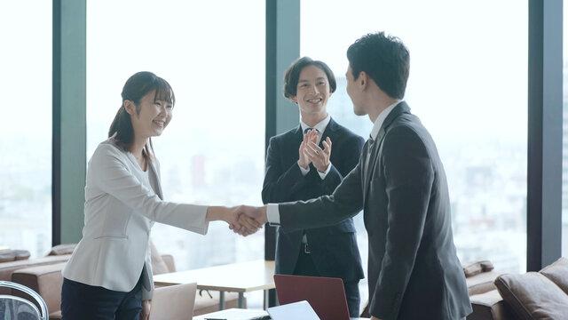 オフィスで握手をするビジネスグループ