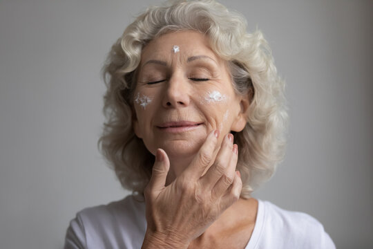 Relaxed elderly woman with closed eyes taking skincare treatment, applying anti age lotion, moisturizer cream on dry face skin with wrinkles. Senior beauty care, cosmetology concept. Close up portrait