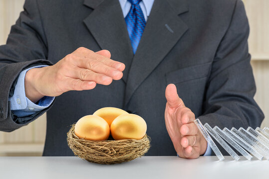 Asset or wealth protection for high net worth individuals, financial concept : Investor uses hands to protect 3 golden eggs, depicting a plan to avoid risk and protect asset for sustainable growth