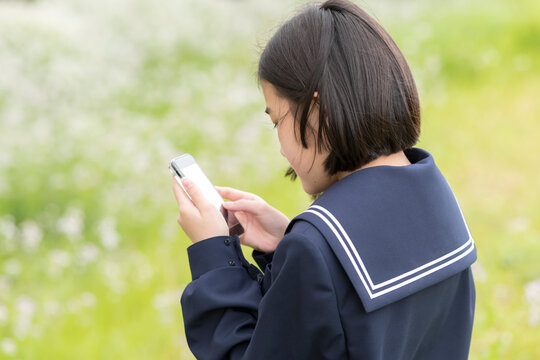 スマホを操作している中学生の女の子