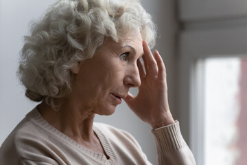 Confused worried old lady suffering from age disorders, Alzheimer disease, headache. Concerned pensive senior 70s woman feeling anxiety, losing memory, having mental disease symptoms. Close up Wall mural