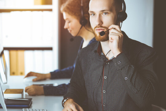 Red-bearded businessman talking by headset near his female colleague while sitting in sunny office. Diverse people group in call center