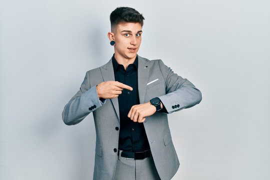 Young caucasian boy with ears dilation wearing business jacket in hurry pointing to watch time, impatience, upset and angry for deadline delay