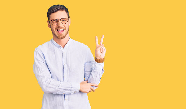 Handsome young man with bear wearing elegant business shirt and glasses smiling with happy face winking at the camera doing victory sign with fingers. number two.
