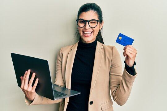 Young hispanic woman wearing business style holding laptop and credit card winking looking at the camera with sexy expression, cheerful and happy face.
