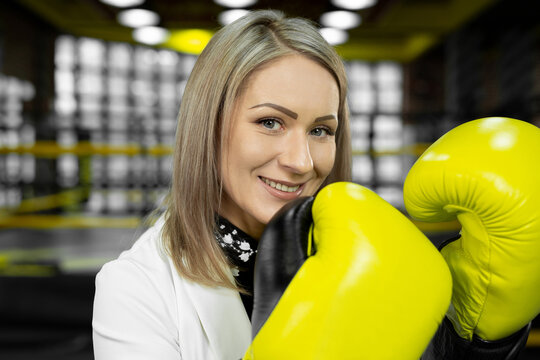 Stylish businesswoman in yellow boxing gloves on the background of a boxing ring looks at the camera and laughs.