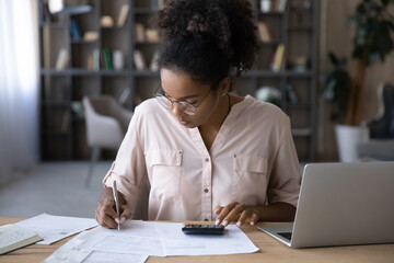 Obraz Serious young biracial woman sit at desk manage budget calculate on machine pay bills taxes online on laptop. Focused African American female count expenses expenditures on calculator. Save concept. - fototapety do salonu