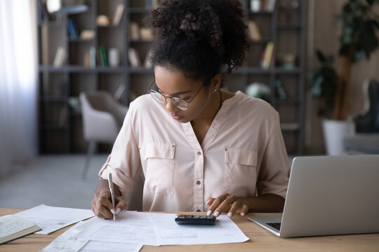 Serious young biracial woman sit at desk manage budget calculate on machine pay bills taxes online on laptop. Focused African American female count expenses expenditures on calculator. Save concept.