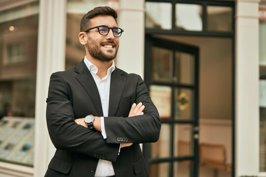 Young hispanic businessman with arms crossed smiling happy at the city.
