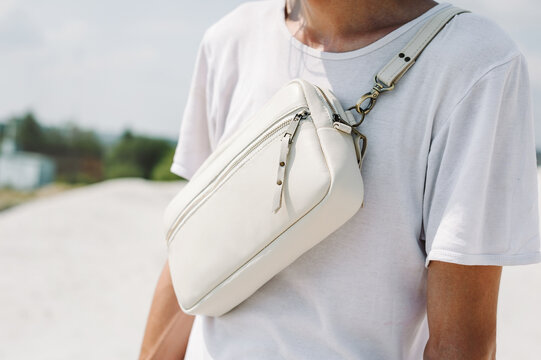 The guy is wearing a white leather bag. Leather sling bag for men Festival bum bag leather.