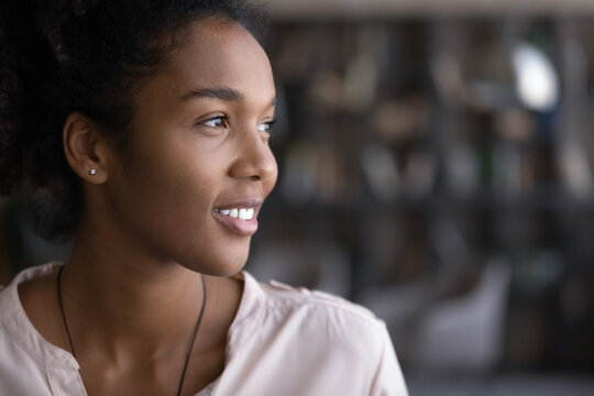 Close up of happy millennial African American woman look in distance thinking or dreaming. Smiling young biracial female imagine or visualize future success or opportunities. Vision, hope concept.