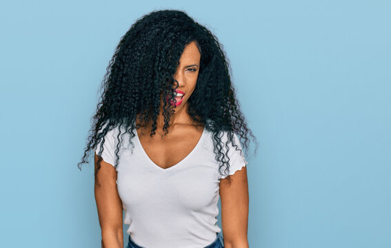 Middle age african american woman wearing casual white t shirt winking looking at the camera with sexy expression, cheerful and happy face.
