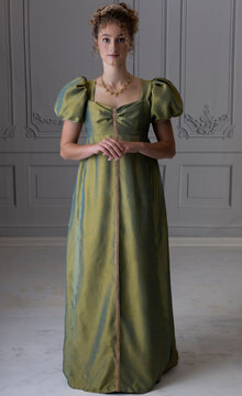 A young Regency woman wearing a green shot silk dress and shown from in front of 3/4 view