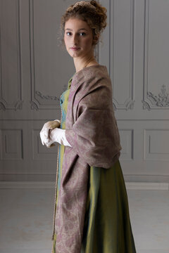 A young Regency woman wearing a green shot silk dress and a paisley shawl