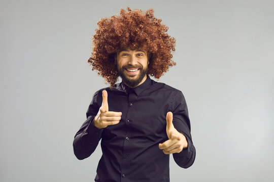 Hey, I choose you. Portrait of funny goofy happy young man in crazy big curly wig pointing index fingers at camera and looking at you standing on gray studio background